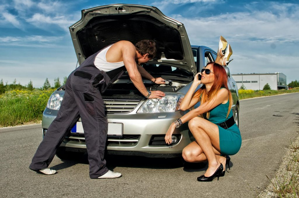 woman sitting while the man is repairing her car