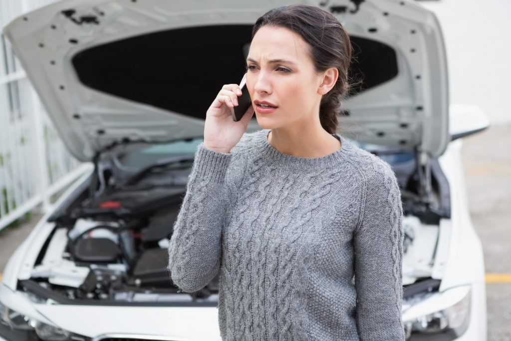 woman calling on someone to repair her car