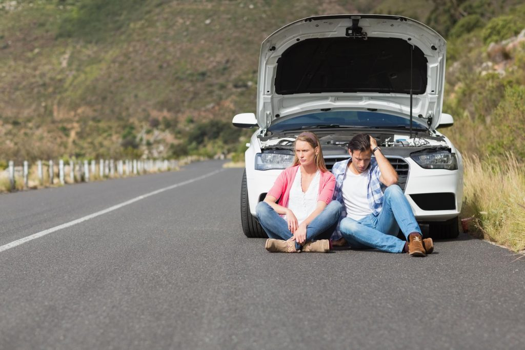 man and woman sitting on the road with their broken car