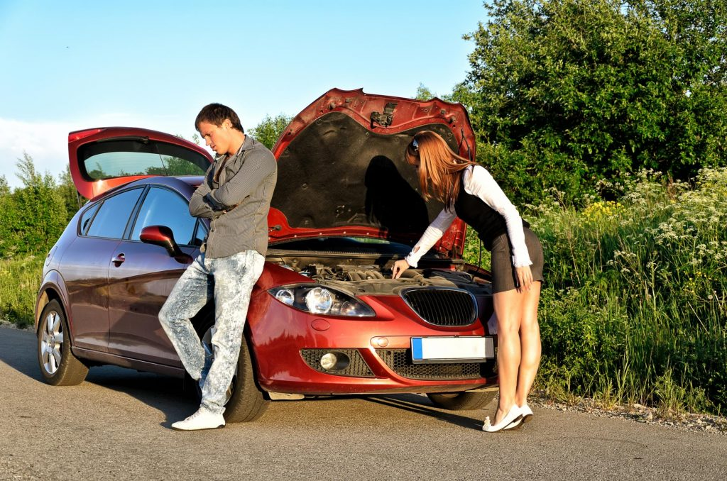 man and woman waiting for someone repair their car